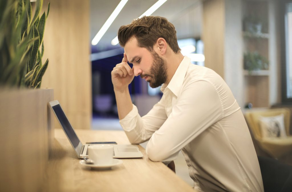 A man taking a moment at his desk at work, feeling depleted from being around draining people.