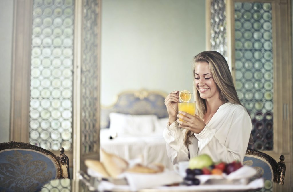 Woman enjoying a healthy drink. Taking care of her body by feeding it healthy food, a form of self care for entrepreneurs - healthy diet.