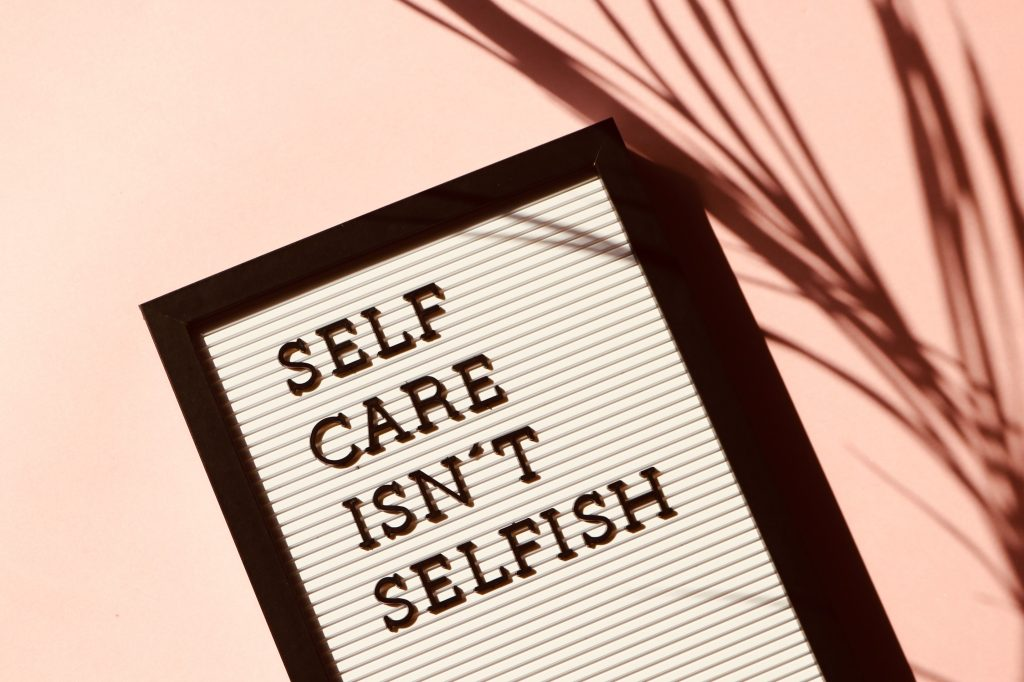 Sign saying 'self care isn't selfish' with self care for entrepreneurs in mind.