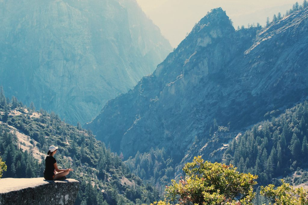 Person sitting at the edge of a cliff looking into a big, expansive valley in beautiful surroundings. Taking some time for themself.