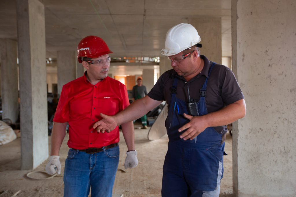 two men walking through a building site, highlighting two people working in business