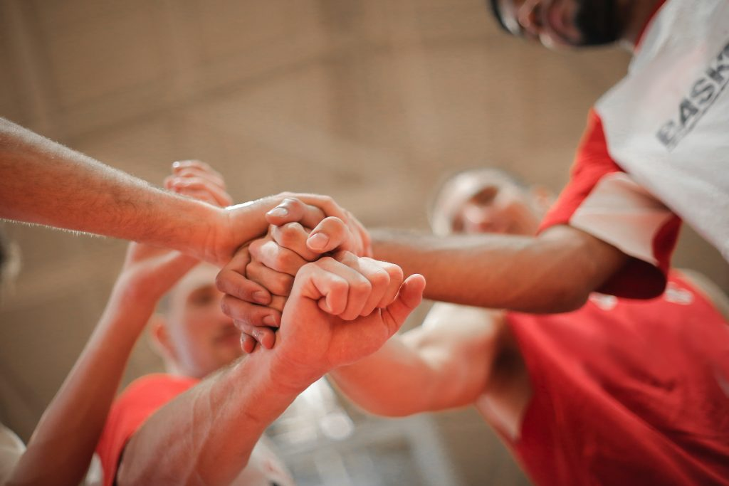 group of hands joining together at a basketball match, symbolising strength