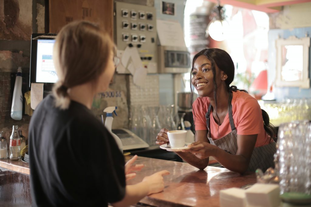 A step towards self-funding a business might be a start business that grows. Here is a woman serving coffee to her customer, as discussed.
