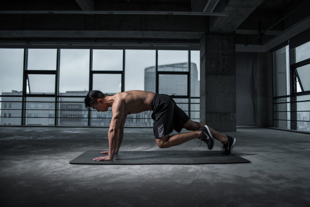 man on a yoga mat doing leg ups in plank position, a physical work out