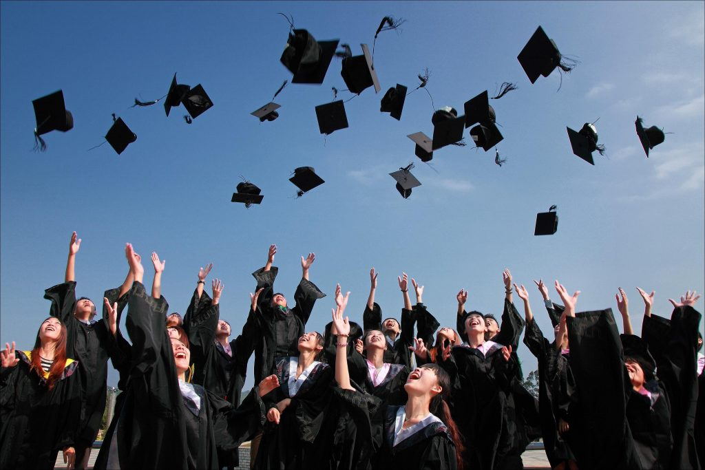 photo of a class in their cap and gown from the back, celebrating their success by throwing their caps in the air