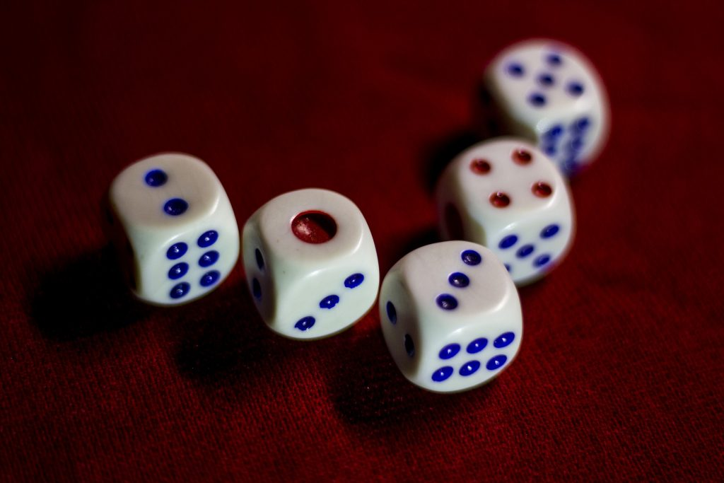 a colour photo of a set of dice. five dice with red and blue dots on it - talking about gambling and game playing in business.