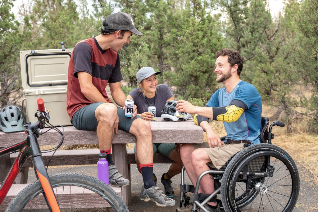picture of three men in their twenties with dark hair all sitting at a wooden bench, one man in a wheelchair. talking about showing up in your personal life reflecting how you show up in you business life as an entrepreneur