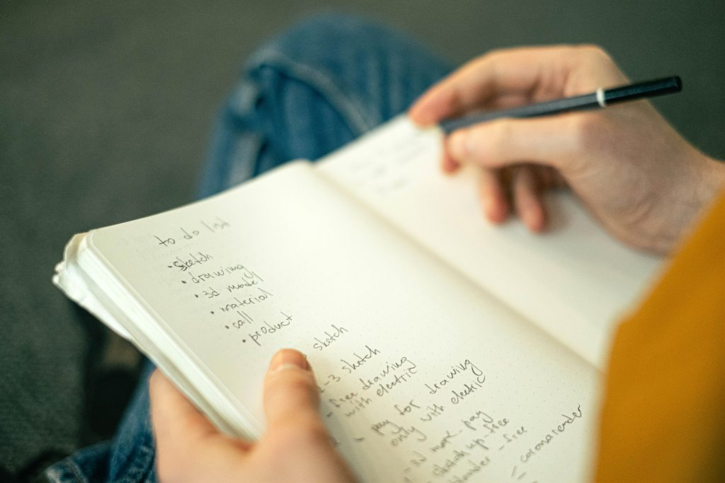 a close up of a man's hands writing into a notebook his to do list