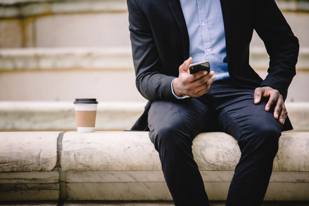 image of a business man sitting on a wall with a take-away coffee beside him, on his smart phone. when making your to do list, it can be easier to do so digitally