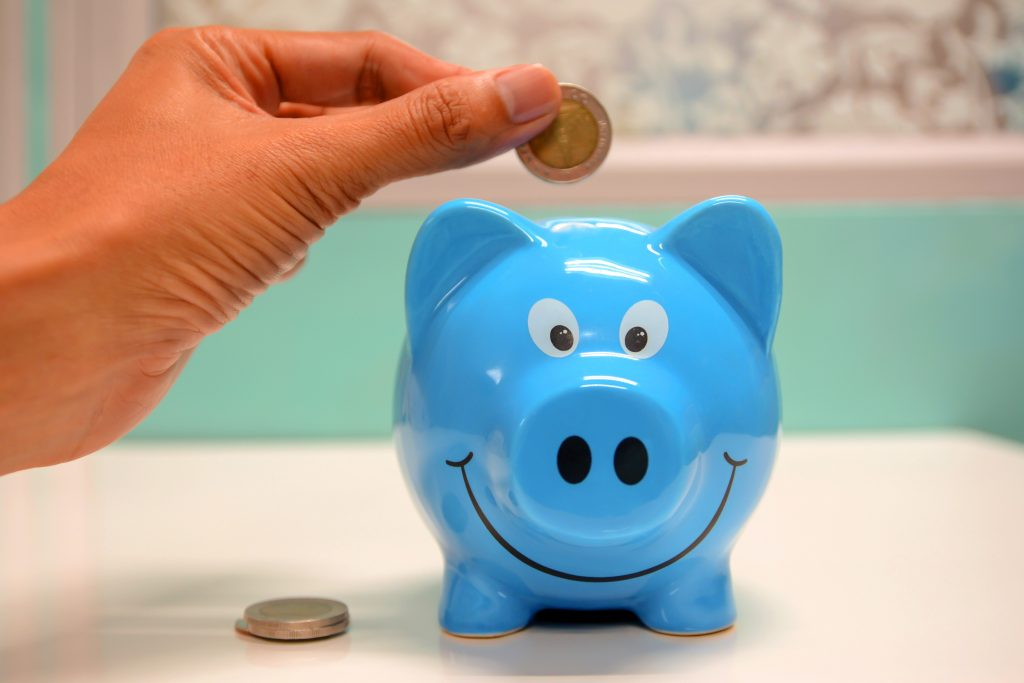 a small blue piggy bank with a person putting a coin in it, signifying the importance of cost in business and the cost of creating a podcast