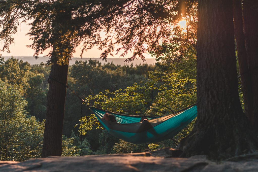 image of a man relaxing in a hammock under the sunset - the benefits of being organised means you can enjoy the moments of relaxation when you know you've done everything you need to do