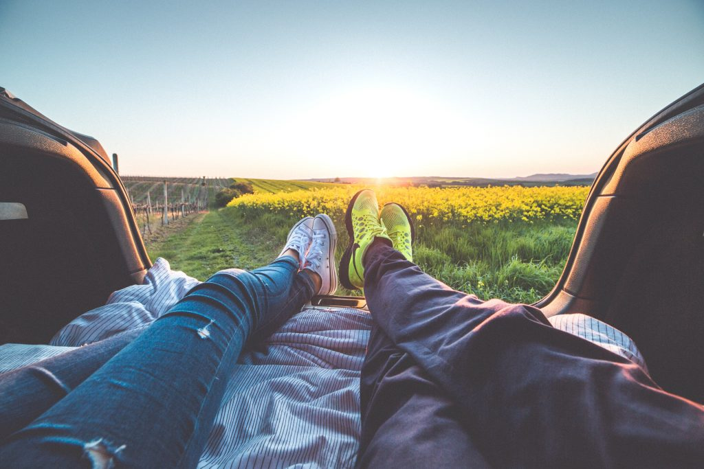 photo of two sets of feet looking out from the back of a pick-up truck onto the horizon. looking ahead
