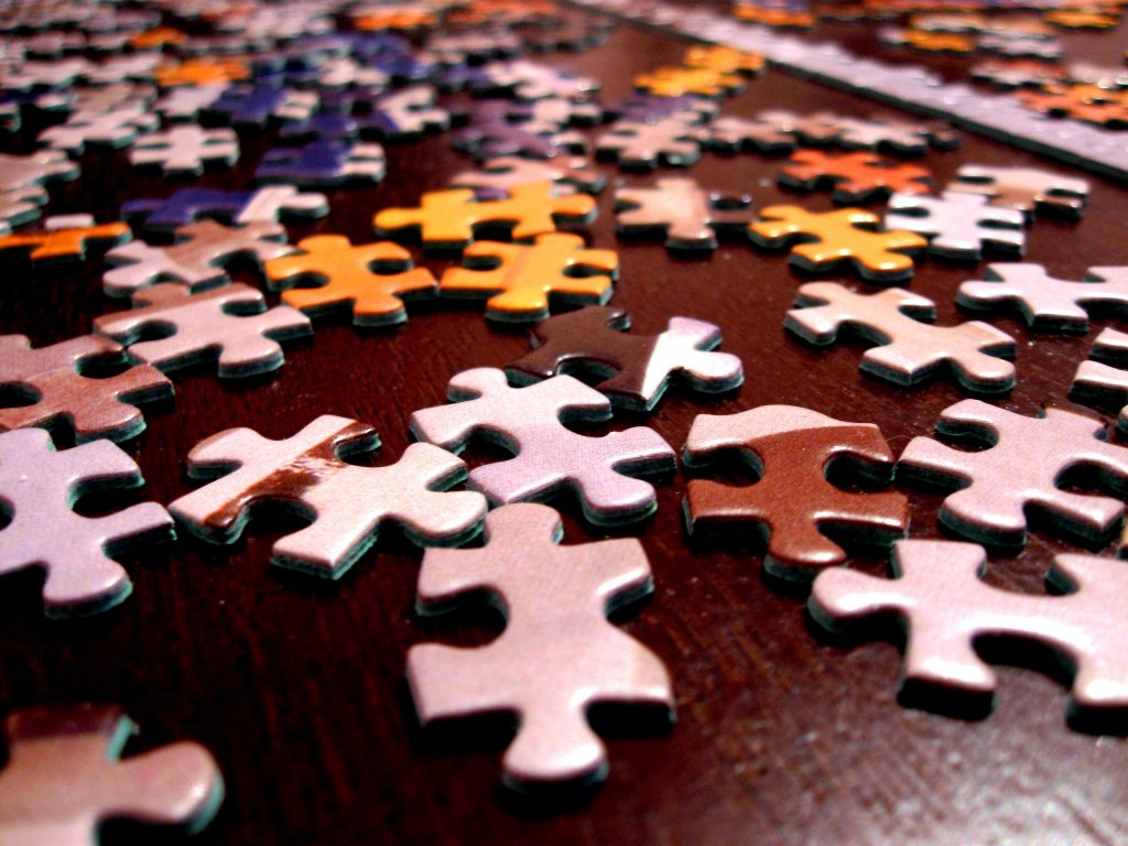 picture of a jigsaw with the pieces all scattered - when thinking about your to do list, think holistically, think of the whole picture