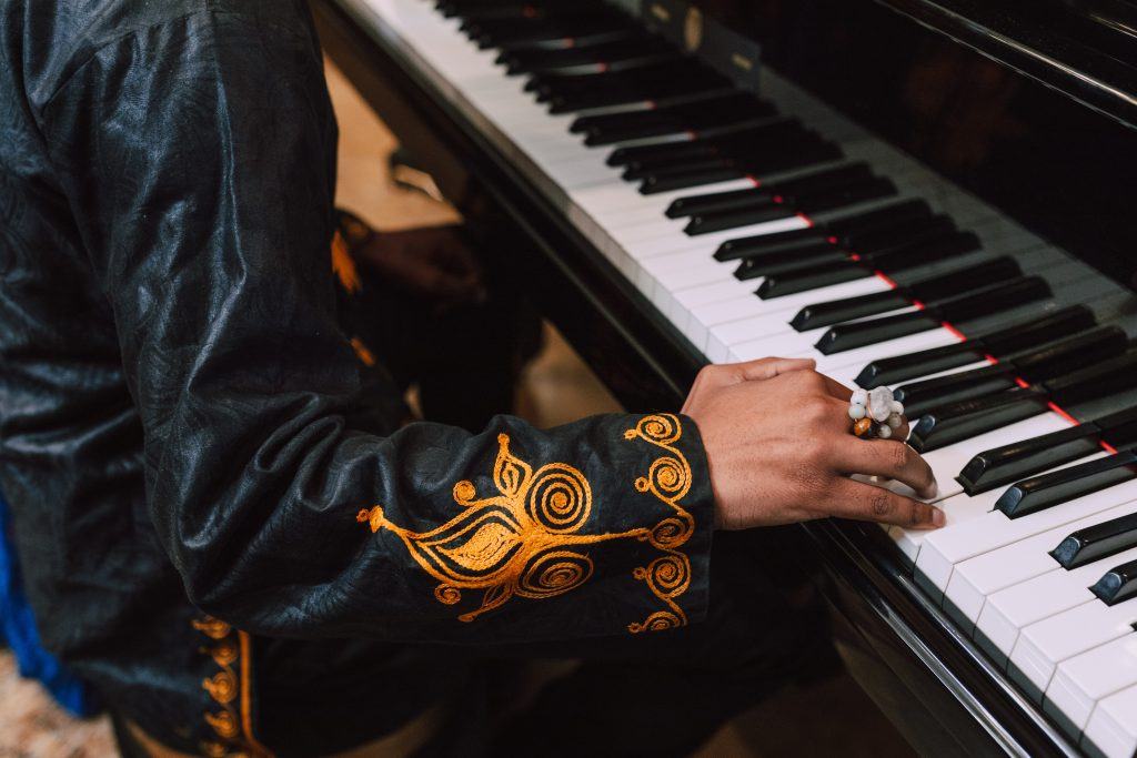 an image of a man playing piano, talking about doing what you love as an entrepreneur. starting a podcast should be in line with you holistically