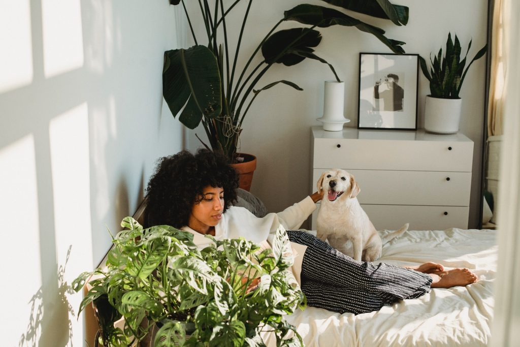 woman and her dog sitting on her bed, relaxing, taking a day off work