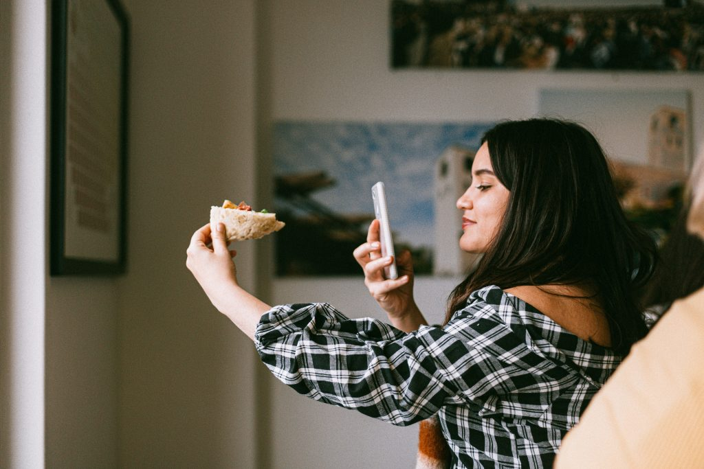 a young woman taking an up close photograph of her good - representing an influencer