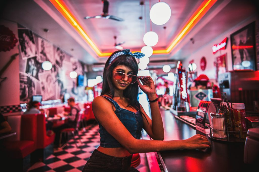 attractive young women influencer sitting at a bar with sunglasses - making money through natural placement of brands