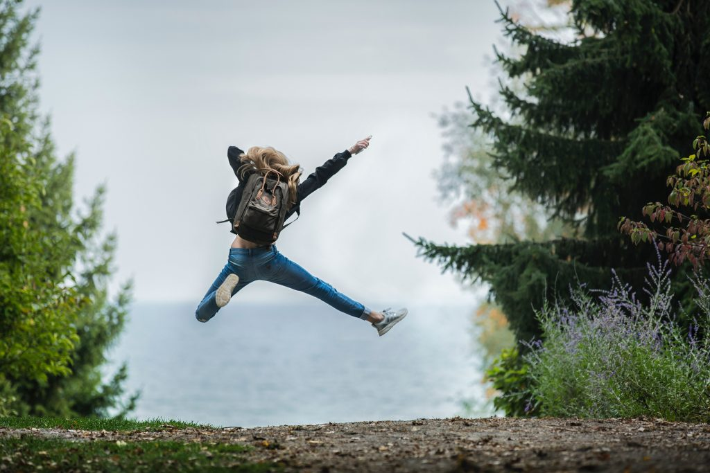 image of a woman on a hike in the forest, jumping in the air - symbolising being full of energy