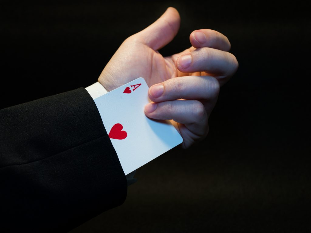 image of a man holding an ace up his sleeve - working holistically gives you an advantage