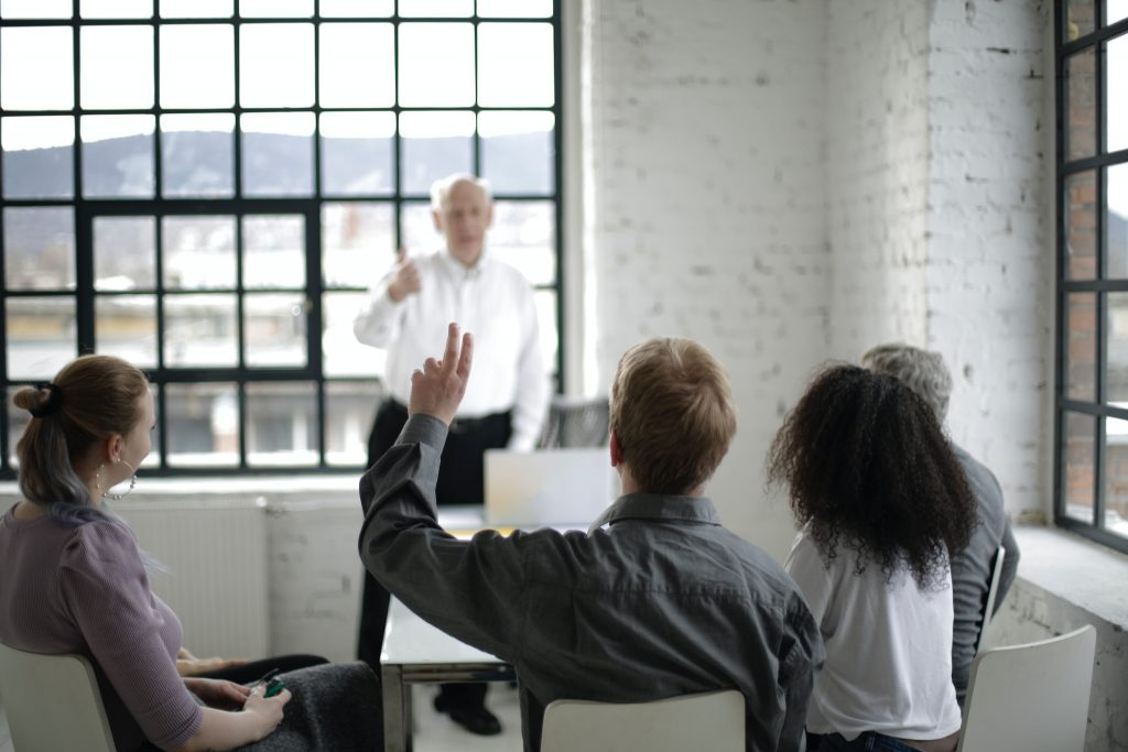 picture of a man giving a talk and a man in the audience with his hand raised