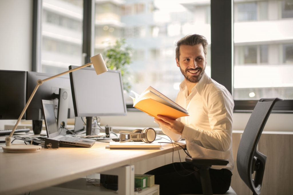 smiling young entrepreneur sitting at his desk swivelling - the benefits of entrepreneurship