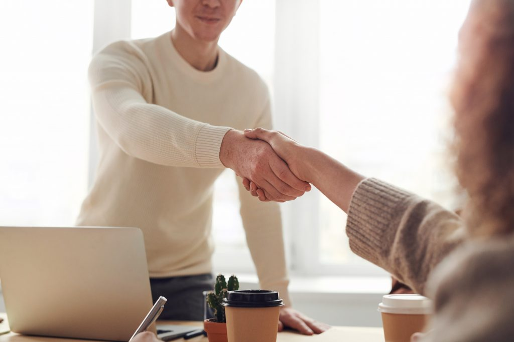 two people shaking hands over a table in an office