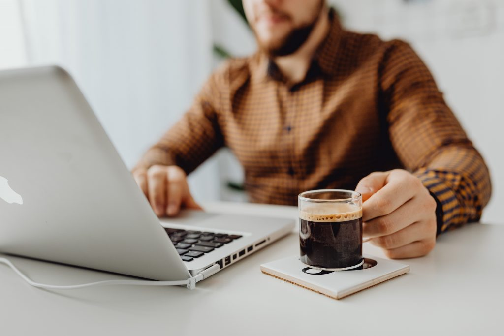 Image of entrepreneur sitting at desk with laptop open and black coffee beside him.
