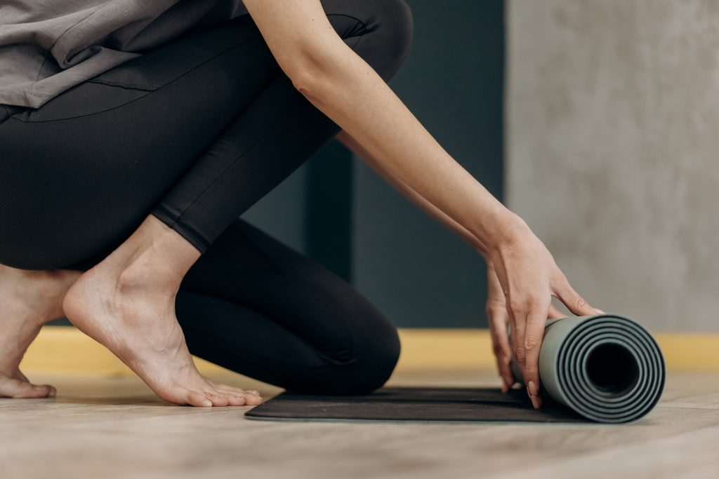 image of woman pulling out a yoga mat -taking