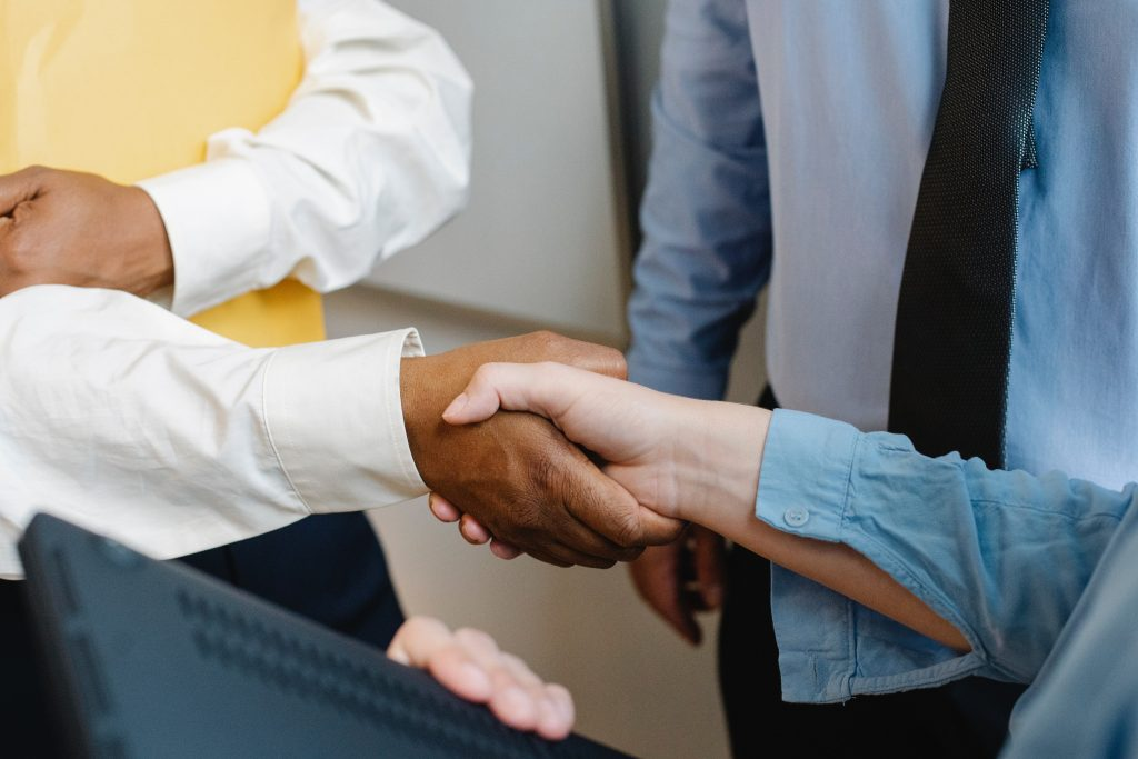 Two people shaking hands - symbolic of agreeing on selling a business